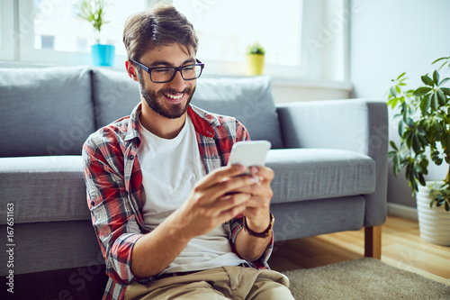Valokuva  Smiling young man sitting on floor and texting friend