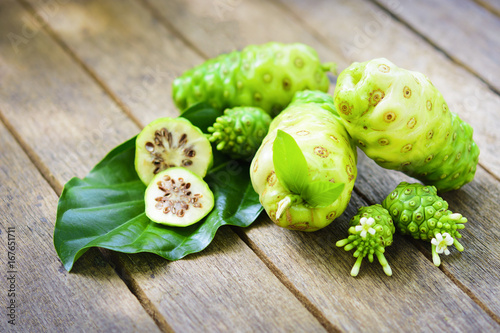 Noni fruit and Noni slice with leaf and blossom on old wooden table Canvas Print
