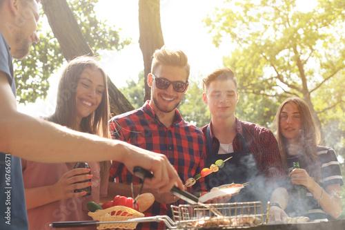 Plakat Szczęśliwi przyjaciele piec na grillu mięso i cieszyć się grilla przyjęcia outdoors.