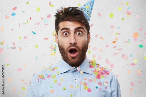 Fotografía  Young Caucasian man dressed in formal shirt and having party cap on head, celebr