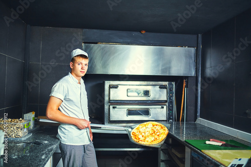 Foto op Aluminium Pizzeria The cook keeps a big pizza