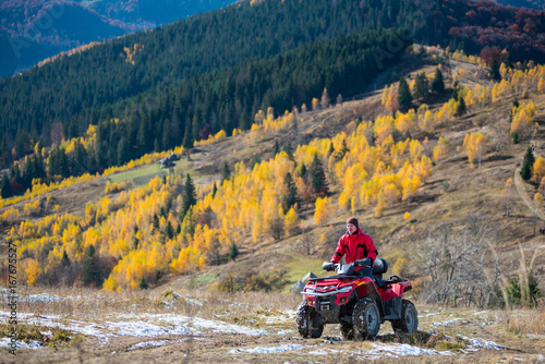 Guy is driving red quad bike on a mountain road passes to the top of the mountain followed by a beautiful landscape of mountains woodlands with a variety of color of the trees green, yellow, red