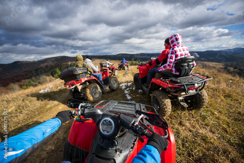View from ATV a group of people riding a quad bikes on a mountain road under a sky with clouds in autumn