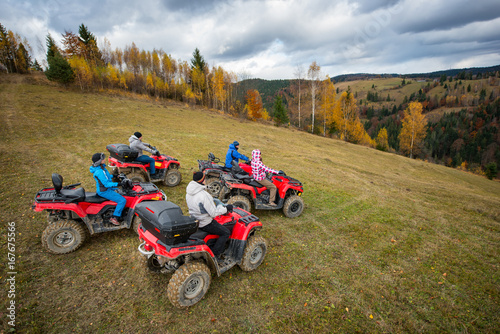 Five ATV riders on off-road quad bikes on the hillside at the background of autumn forest with colorful trees and mountains. Top view