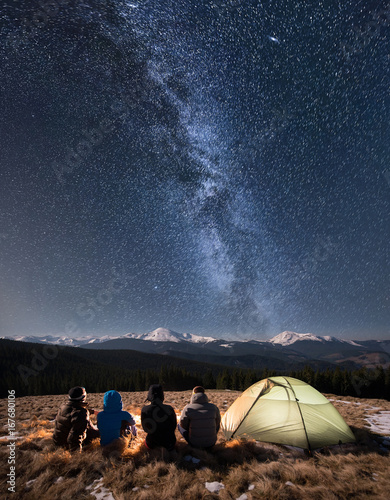 Deurstickers Kamperen Rear view of four people sitting together beside camp and tent under beautiful night sky full of stars and milky way. On the background snow-covered mountains. Long exposure