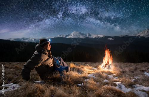 Obraz Male tourist have a rest in the mountains at night. Guy with a headlamp sitting near campfire under beautiful night sky full of stars and milky way, and enjoying night scene - fototapety do salonu