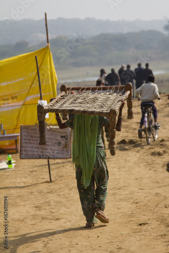 Fotografie, Obraz Female villager carrying a jute cot bed on her head near the Damdama lake area i