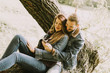 Couple in love sitting on a tree in autumn park and using mobile phone