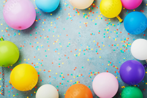 Colorful Balloons And Confetti On Blue Table Top View Birthday
