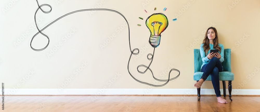 Fototapety, obrazy: Light bulb with young woman holding a tablet computer in a chair