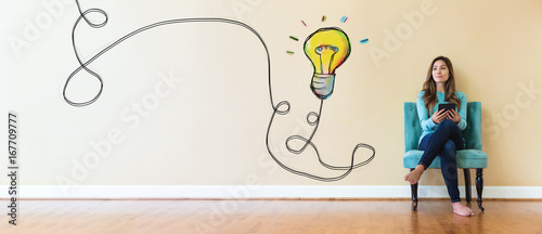 Light bulb with young woman holding a tablet computer in a chair Canvas Print