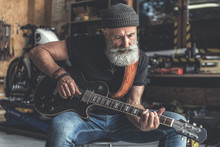 Concentrated Elder Man Holding Instrument