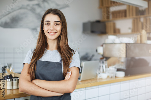 Fotografie, Obraz  Pastry and coffee shop owner looking confident smiling at camera with arms crossed