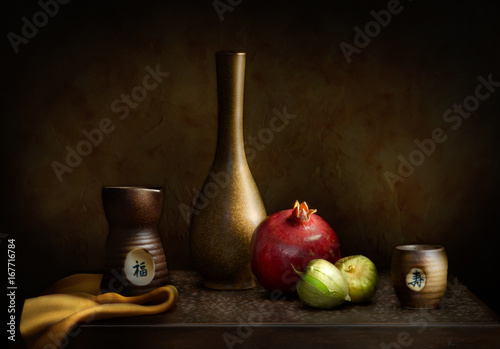 Fototapeta Still life with pomegranate, tomatillos, and sake set obraz