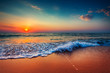 Beautiful sunrise over the sea and breaking ocean wave