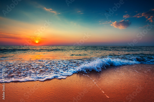 Staande foto Strand Beautiful sunrise over the sea and breaking ocean wave