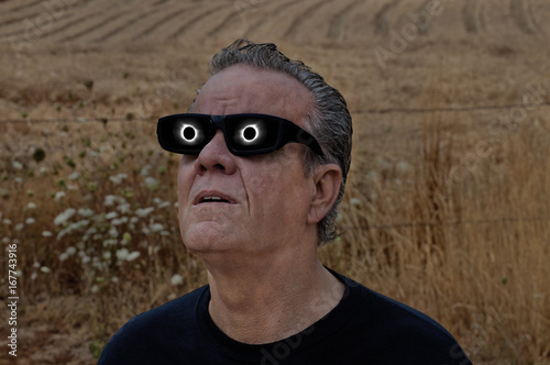 Man looking at full solar eclipse with eclipse reflecting in lenses/Man viewing full solar eclipse with solar glasses in country field/