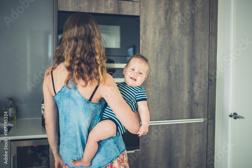 Mother with baby in kitchen Wallpaper Mural