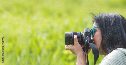 Woman photographer wear sunglasses and holding camera and