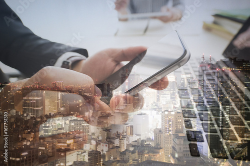 Obraz na plátne  The hands of businessmen who have smartphones and city photos