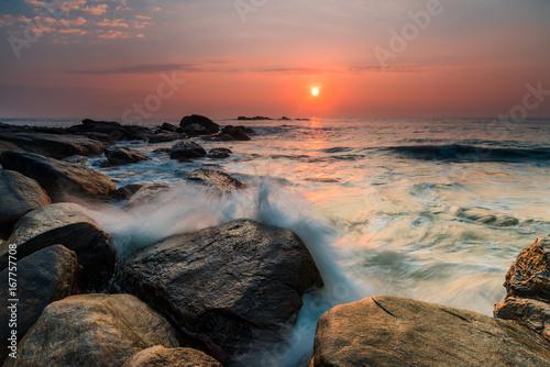 Fotobehang Landschap Sunset on the rocky shore of tropical sea