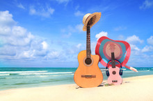Sweet Classic Guitar And Pink Ukulele,hat, Headphones,football On Blue Sky And Beach Background