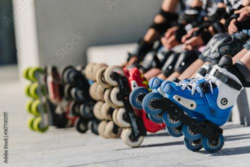 Feet of rollerbladers wearing inline roller skates sitting in outdoor skate park, Close up view of wheels befor skating