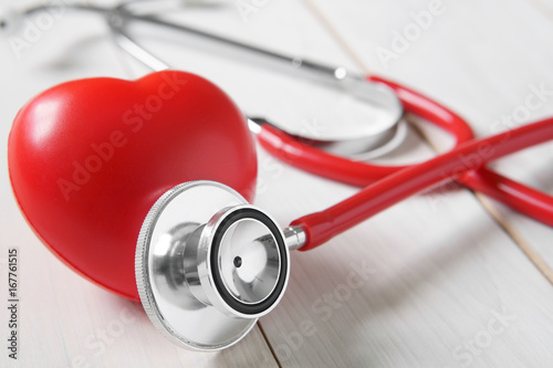 Fotografía  closeup red heart rubber with stethoscope medical instrument on vintage white wo