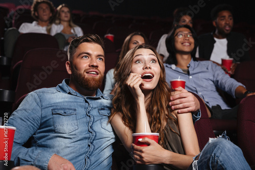 Foto Surprised young couple sitting at the cinema