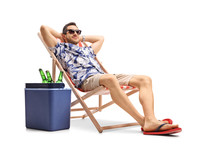 Tourist Relaxing In A Deck Chair Next To A Cooling Box