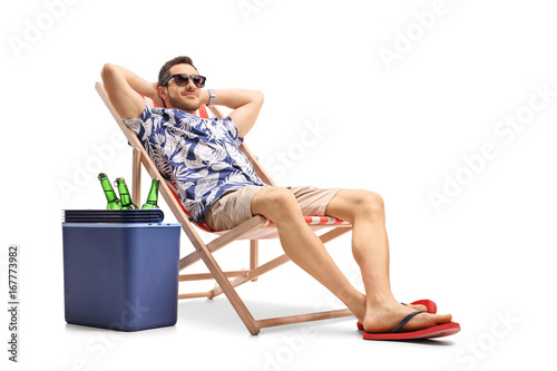 Foto Tourist relaxing in a deck chair next to a cooling box