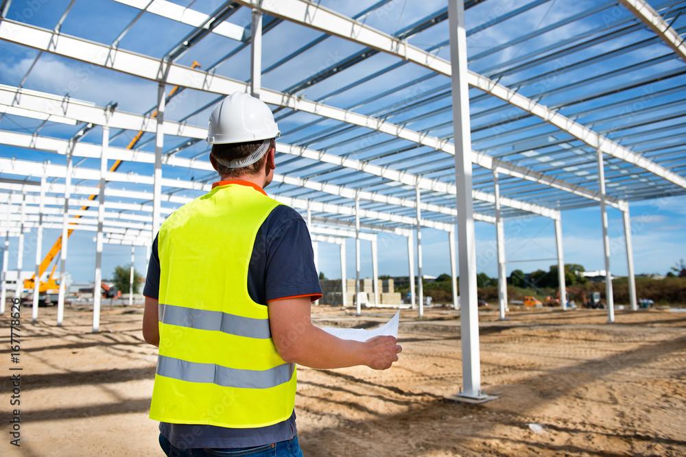 Fototapeta Kierownik budowy hali produkcyjnej stalowej z planem w rękach