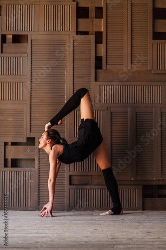 Fotografie, Obraz  young girl doing gymnastics on the wood background