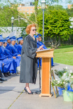 Principle Standing At Podium, Giving Speech, On Graduation Day. Students Sitting In Rows Behind