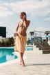 Beautiful woman near open water pool in hotel on tropical resort