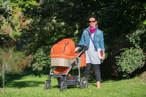 Mama z wózkiem podczas spaceru w parku Canvas Print