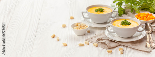Fotografía  Pumpkin cream soup with croutons, raw fresh pumpkin pieces and herbs on a white rustic wooden background, Autumn concept
