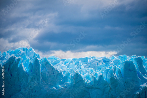 Fotografía  Uneven blue glacier against the background of a cloud in the sky