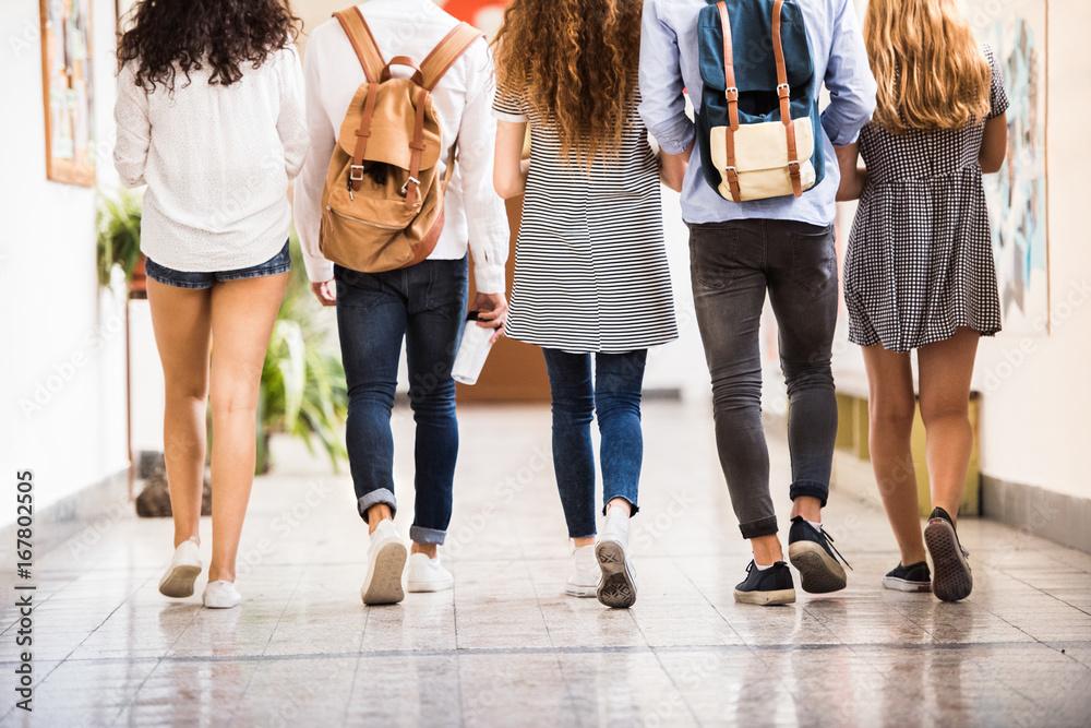 Fotografía Unrecognizable teenage students in high school hall.