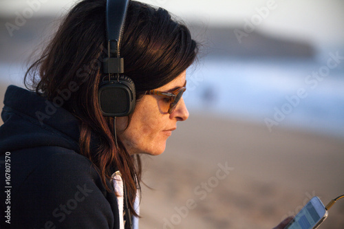 Papiers peints Magasin de musique Mid adult woman sitting on beach and listening to music