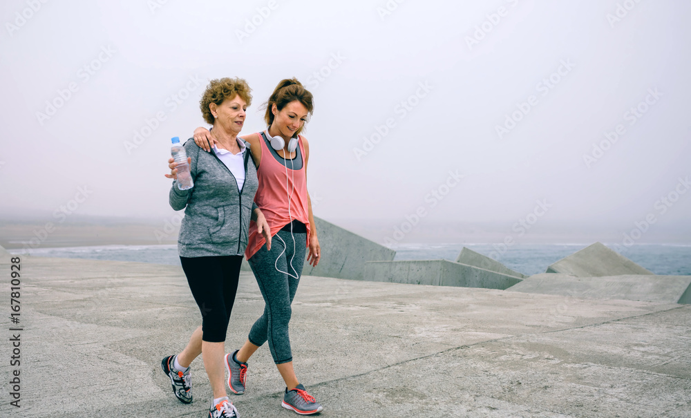 Fototapety, obrazy: Senior woman and young woman walking outdoors by sea pier