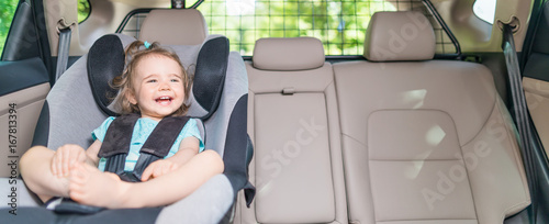 Fotomural  Infant baby girl buckled into her car seat.