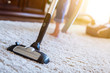 canvas print picture - Woman using a vacuum cleaner while cleaning carpet in the house.