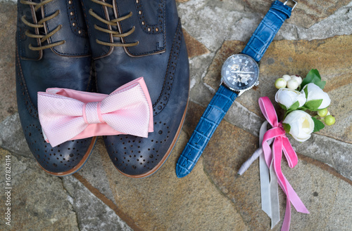 1bdc7ecc3e50 Top view of pink bowtie on blue leather groom shoes near watches and  boutonniere on brown natural stone. Groom wedding accessories. Man watches,  bow-tie, ...