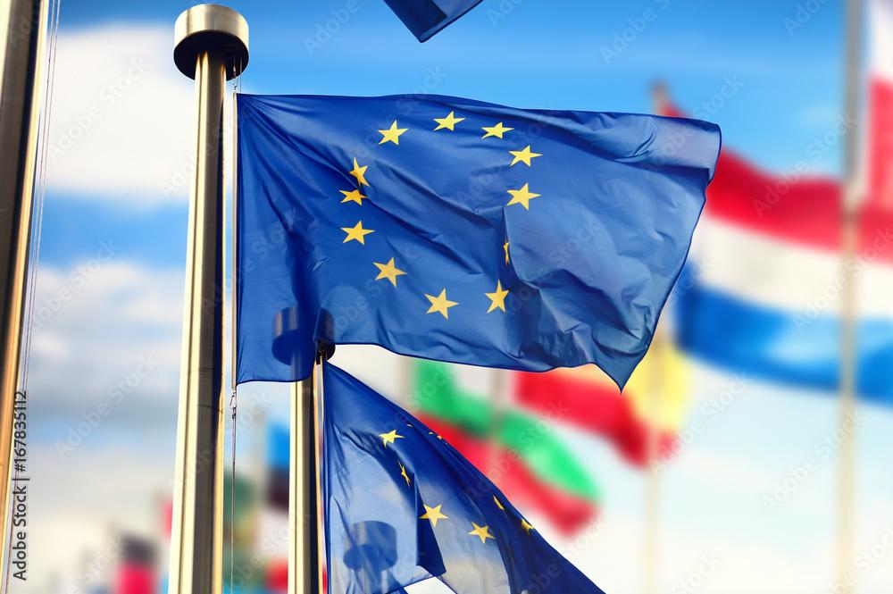 Fototapeta EU flags waving over blue sky. Brussels, Belgium