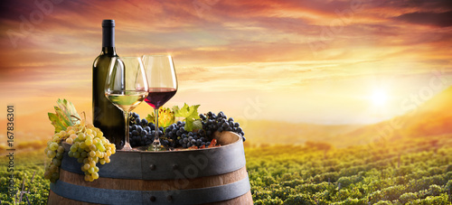 Tuinposter Honing Bottle And WineGlasses On Barrel In Vineyard At Sunset