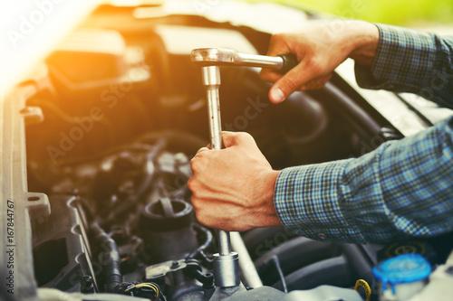 Zdjęcie XXL Auto mechanik pracuje z kluczem w silniku. Usługa naprawy samochodów