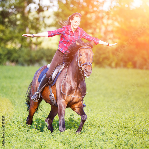 Fotografia Happy young woman riding galloping horse at sunny summer day
