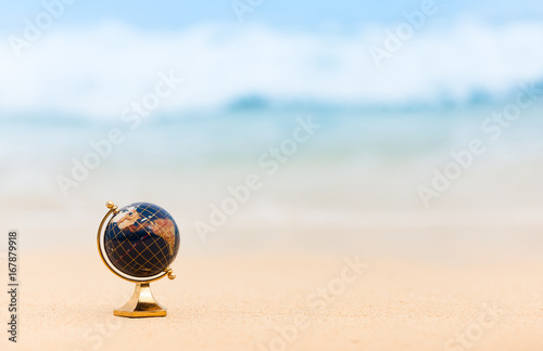 Foto op Canvas Wereldkaart World travel concept. Globe on the beach.