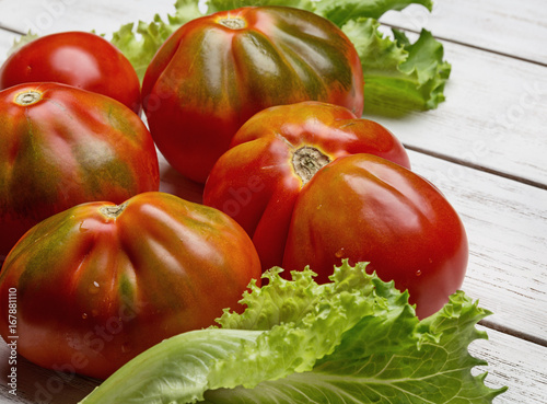 Red tomatoes and salad on white wooden board Poster